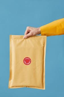 Close-up van postbode bedrijf pakket verpakt in papier geïsoleerd op blauw