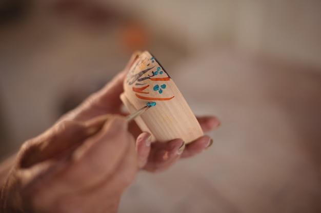 Close-up van pottenbakker schilderen op kom