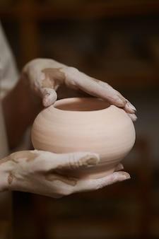 Close up van pottenbakkers handen in klei en met een nieuwe kom
