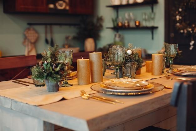 Close-up van prachtig ingerichte eettafel met sparren in vazen en gouden kaarsen. bordensets voor vier personen.