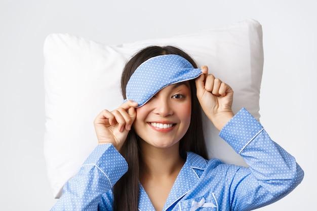 Close-up van prachtig jong aziatisch meisje in blauwe pyjama, slaapmasker opstijgen om met een gelukkige glimlach naar iets interessants te gluren, liggend op een kussen in bed, wakker worden met verrassing, witte achtergrond. Premium Foto