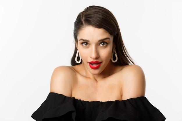 Close-up van prachtige brunette vrouw, gekleed in elegante oorbellen en zwarte jurk, sensueel kijkend naar camera met doordringende blik en geopende mond, staande op witte achtergrond