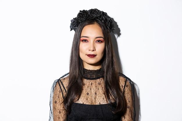 Close-up van prachtige gotische meisje met zwarte krans, aankleden voor halloween-feest, staande op witte achtergrond in boos heks kostuum.