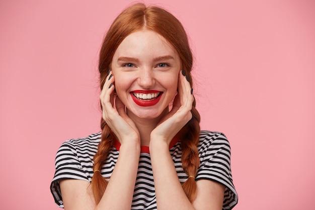 Close-up van prachtige mooie roodharige meisje met twee vlechten houdt handen in de buurt van haar gezicht en lacht levendig met rode lippen, witte gezonde tanden tonen, geïsoleerd