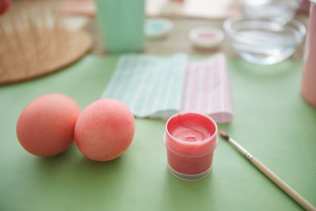 Close up van prachtige pastel roze eieren op tafel in kunststudio naast kwast, ester decoraties concept, kopie ruimte