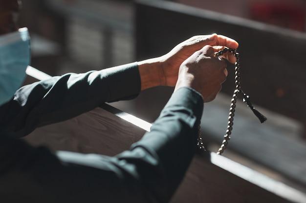 Close-up van priester met masker die rozenkranskralen vasthoudt terwijl hij voor het altaar zit