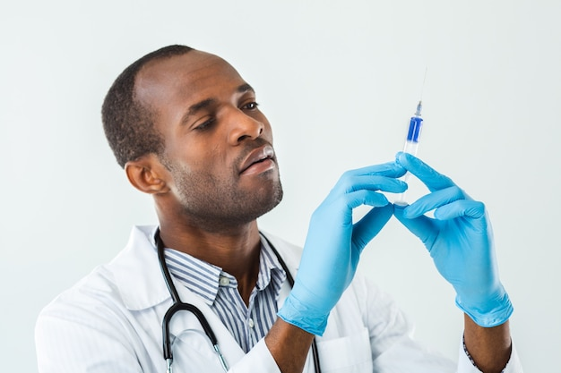 Close-up van professionele afro-amerikaanse arts met behulp van een spuit terwijl hij tegen een witte muur staat
