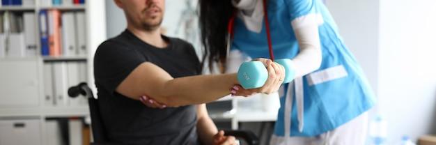 Close-up van professionele arts die patiënt helpt om gewonde arm uit te werken. verpleegster in uniform werken. man zit in rolstoel. moderne geneeskunde en ziekenhuisconcept