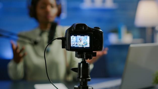 Close up van professionele camera zit voor dslr opname online show. afrikaanse vrouwenvlogger die bij microfoon spreekt tijdens livestreaming, blogger die in podcast bespreekt die hoofdtelefoons draagt