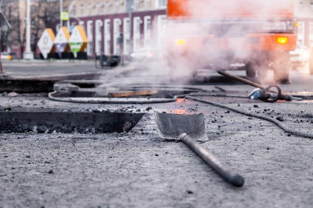 Close-up van professionele hulpmiddelen voor asfaltreparatie, wegkuil, schop, bitumen tegen stadsachtergrond.