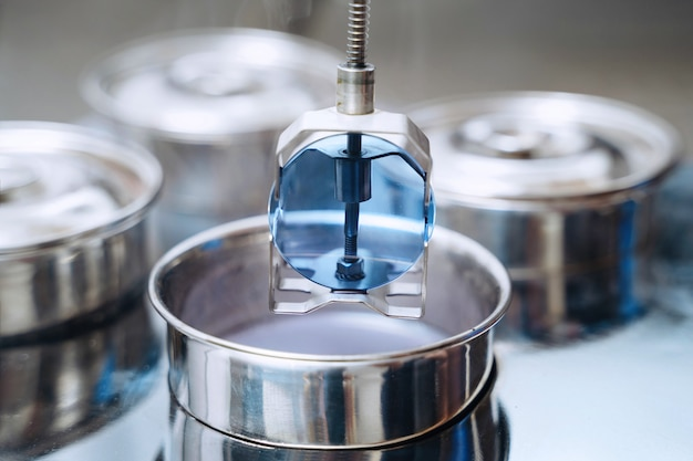 Close-up van professionele kleuring van brillenlens in optische fabriek of werkplaats door opticientechnicus met speciaal gereedschap en apparatuur