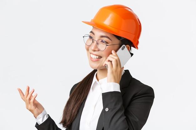 Close-up van professionele lachende aziatische vrouwelijke ondernemer in fabriek, hoofdingenieur in veiligheidshelm en pak, praten over de telefoon, zakelijk gesprek voeren met investeerders van onderneming