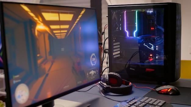 Close-up van professionele monitor met first person shooter-videogame aan. thuisstudio van esport-videogamespeler die krachtige spelcomputer gebruikt tijdens online competitie