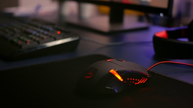 Close-up van professionele muis met rgb-verlichting tijdens online shooter-videogamestoernooi. thuisstudio van esport-videogamespeler met krachtige gaming-pc