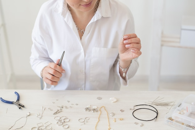 Close-up van professionele sieradenontwerper die handgemaakte sieraden maakt in de close-upmode van de studioworkshop