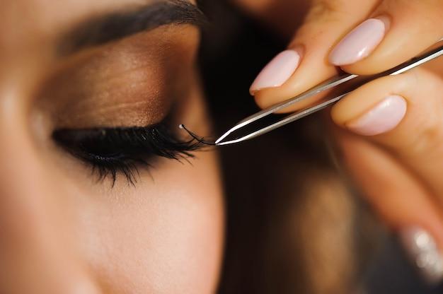 Close up van professionele stylist wimpers verlengen voor vrouwelijke cliënt in een schoonheidssalon.