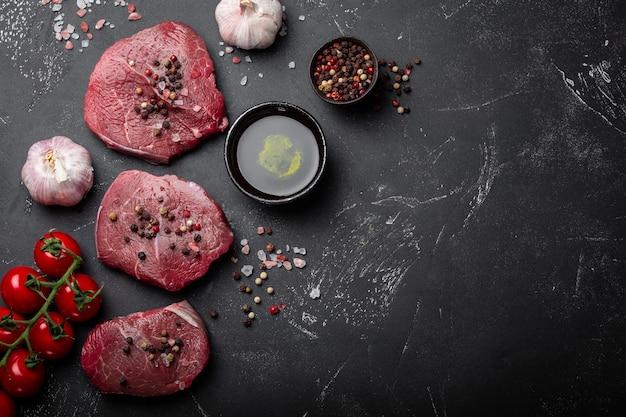 Close-up van rauw vers gemarmerd vlees steak op donkere rustieke betonnen achtergrond met kruiden, olijfolie, knoflook, tomaten klaar om te worden gekookt. koken vlees filet concept met ruimte voor tekst, bovenaanzicht