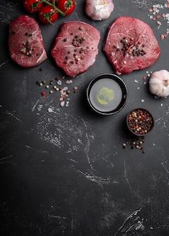 Close-up van rauw vers gemarmerd vlees steak op donkere rustieke betonnen achtergrond met zout en peper, olijfolie, knoflook klaar om te worden gekookt. koken vlees concept met ruimte voor tekst, bovenaanzicht
