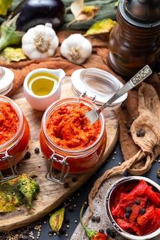 Close-up van rauwe ajvar op tafel met groenten en sauzen op de achtergrond