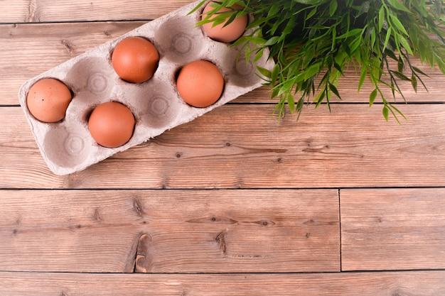 Close-up van rauwe kippeneieren in een eierdoos op een houten achtergrond, een bloem in een pot. kopieer ruimte.