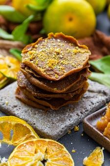Close-up van rauwe pannenkoeken met citrus toppings op een tafel omgeven door droge mandarijnen