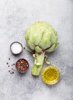 Close-up van rauwe verse artisjok met kruiden klaar om te koken, geweldig als vegetarisch voedsel of ingrediënt voor gezonde salades en diëten, grijze steen rustieke achtergrond