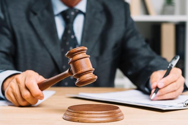 Close-up van rechter die oordeel geven door hamer bij bureau te raken