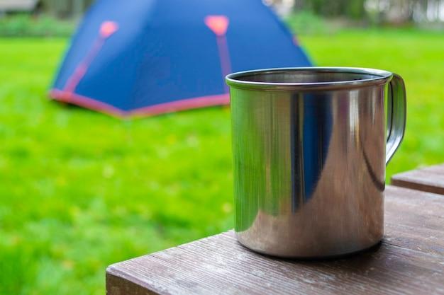 Close-up van reisbeker. metalen mok met thee of koffie op houten tafel.