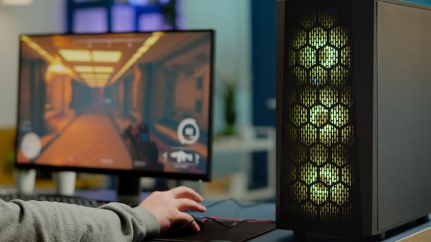 Close up van rgb krachtige computer gamer rig met first-person shooter game op het scherm, pro cyber man die deelneemt aan online esports kampioenschap. speler presteert op gamingtoernooi in cyberspace