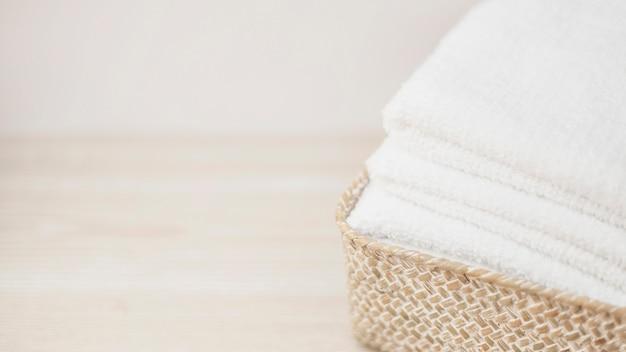 Close-up van rieten mand met gestapelde handdoeken