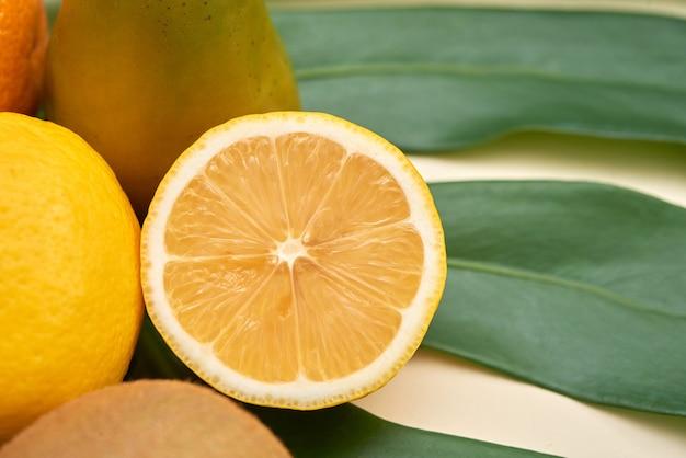 Close-up van rijpe citroen gesneden in de buurt van ander fruit op groen blad, citrus concept