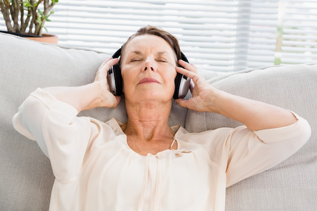 Close-up van rijpe vrouw die aan muziek luistert