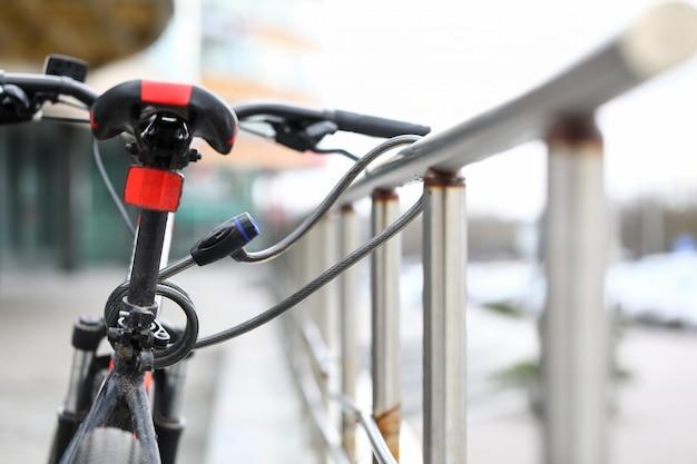 Close-up van rode fiets en beschermingsslotkoord op metaalleuning. vaste versnelling voor transport. straat parkeren buiten. veiligheid en voertuigbeveiliging concept