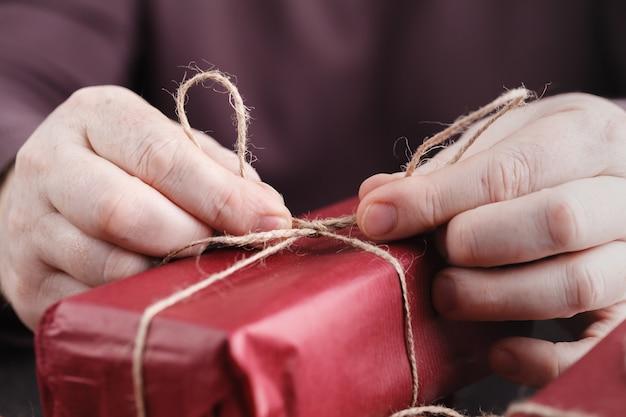 Close-up van rode geschenkdoos. kerstcadeaus inpakken, mensen decoreren cadeautjes. vakantie, handgemaakt, liefde, verrassingsconcept