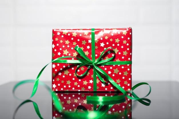 Close-up van rode geschenkdoos met groene strik op zwart glas