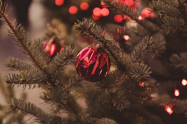 Close up van rode glitter kleur ballen op kerstboom. bokehslingers op de achtergrond.