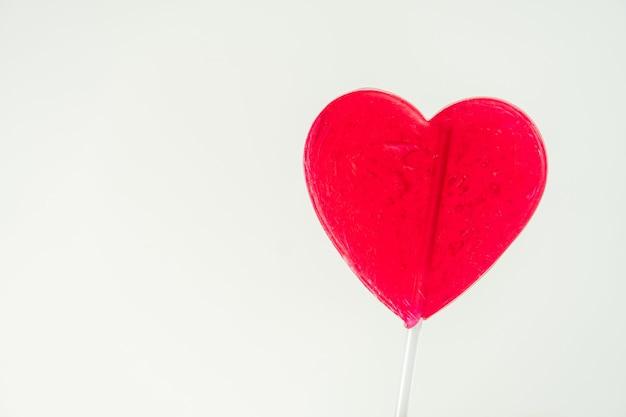 Close-up van rode hartvormige lolly met witte achtergrond