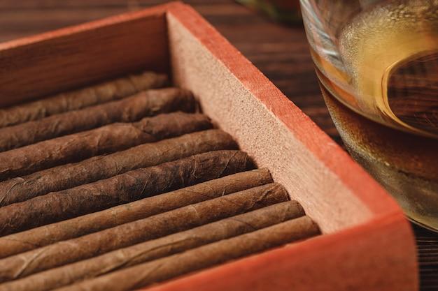 Close-up van rode houten doos met gerolde sigaren op houten tafel