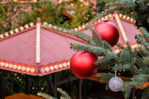 Close-up van rode kerstballen en slinger op een takken van natuurlijke nieuwjaarsboom op feestelijk versierde stadsmarkt buiten op winterdag. geen mensen, geen sneeuw.