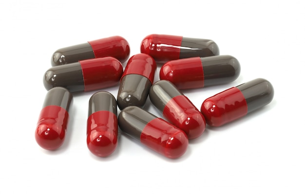 Close-up van rode medische capsules die op witte muur worden geïsoleerd