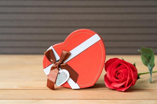 Close-up van rode rozen en hartvormige doos op hout achtergrond, valentijnsdag concept met rozen en rode hartvormige doos