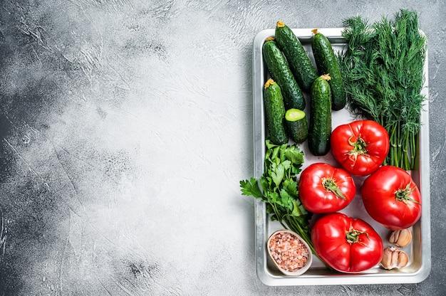 Close-up van rode tomaten en groene komkommers met kruiden in een keukendienblad. witte achtergrond. bovenaanzicht. ruimte kopiëren.
