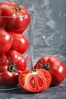 Close-up van rode tomaten met een glazen vaas op een grijze achtergrond. kopieer ruimte, abstractie, verse groenten.