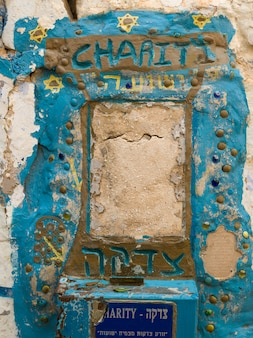Close-up van roestige liefdadigheidsdoos op muur, oude stad, safed, noordelijk district, israël