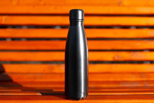 Close-up van roestvrij thermo waterfles zwart op achtergrond van oranje houten bankje. herbruikbare flessen nul afval eco-concept.