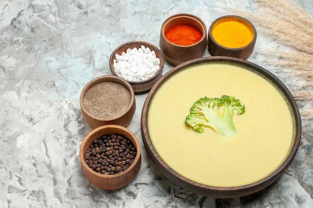 Close-up van romige broccolisoep in een bruine kom en verschillende kruiden op grijze tafel