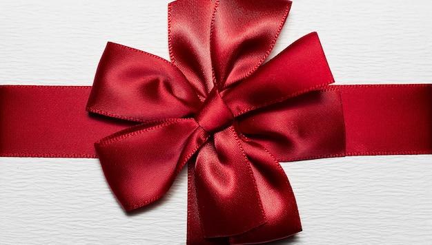 Close-up van rood inwikkeling lint in vorm van boog voor witte geschenkdoos.