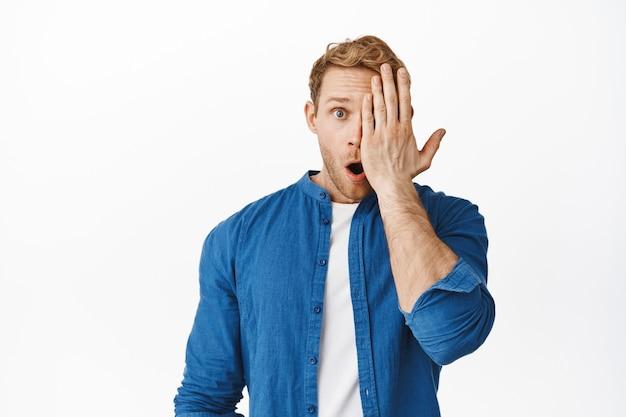 Close-up van roodharig mannelijk model kijkend met één oogkant van gezicht en laat de kaak vallen, hijgend verbaasd, zeg wow, geweldige advertentieaanbieding bekijkend, staande over witte muur