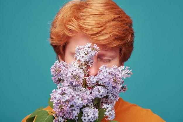 Close-up van roodharige man zonder allergie die de ogen gesloten houdt terwijl hij lila op blauw ruikt, bloesemconcept