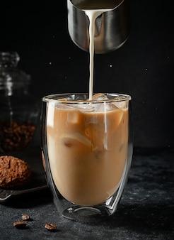 Close-up van room gieten in het glas ijskoffie